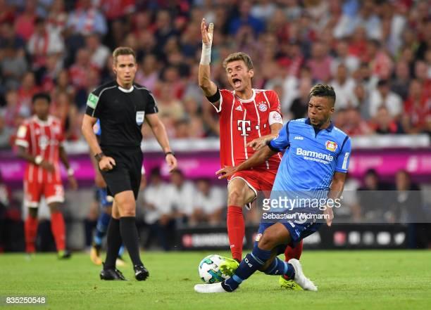 Benjamin Henrichs of Bayer Leverkusen with Thomas Mueller of Bayern Muenchen while referee Tobias Stieler looks on during the Bundesliga match...