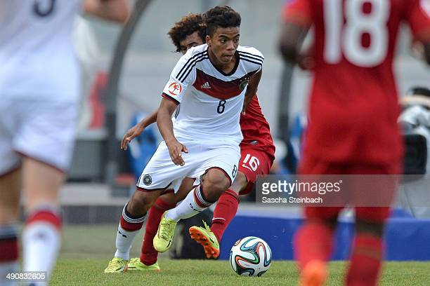Benjamin Henrichs of Germany is challenged by Diogo Izata of Portugal during the UEFA Under17 European Championship 2014 group B match between...