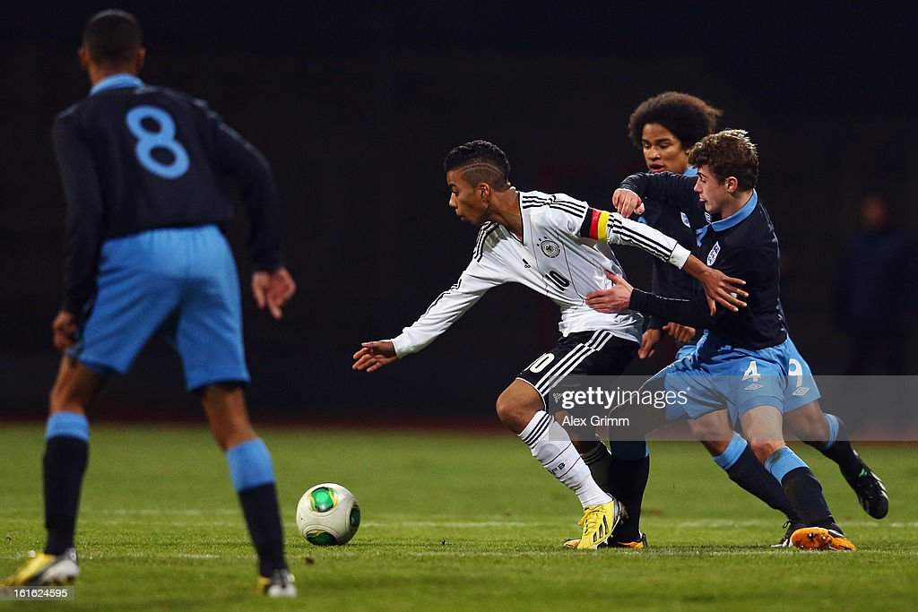 Benjamin Henrichs (C) of Germany is challenged by Ryan Ledson, Isaiah Brown and Max Lowe of England during the U16 international friendly match between Germany and England at Suedstadion on February 13, 2013 in Cologne, Germany.