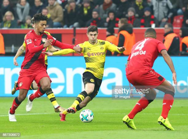 Benjamin Henrichs of Leverkusen Christian Pulisic of Dortmund and Jonathan Tah of Leverkusen battle for the ball during the Bundesliga match between...