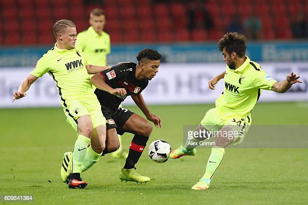 Benjamin Henrichs of Leverkusen is challenged by Alfred Finnbogason and Jan Moravek of Augsburg during the Bundesliga match between Bayer 04...