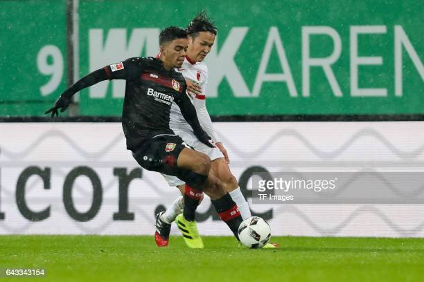 Benjamin Henrichs of Leverkusen und Takashi Usami of Augsburg battle for the ball during the Bundesliga match between FC Augsburg and Bayer 04...
