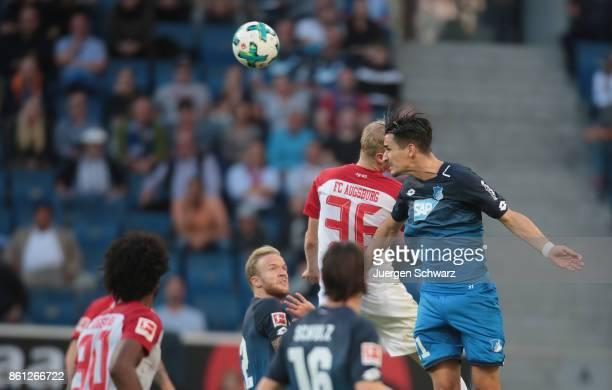 Benjamin Huebner of Hoffenheim and Martin Hinteregger of Augsburg jump for of Augsburg header during the Bundesliga match between TSG 1899 Hoffenheim...
