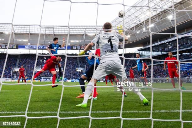 Benjamin Huebner of Hoffenheim scores his team's first goal with a header past Lukas Hradecky of Frankfurt during the Bundesliga match between TSG...