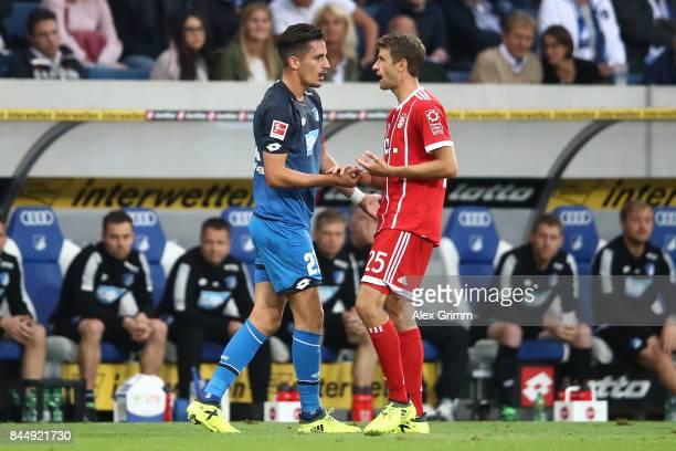 Benjamin Huebner of Hoffenheim talks with Thomas Mueller of Bayern Muenchen during the Bundesliga match between TSG 1899 Hoffenheim and FC Bayern...