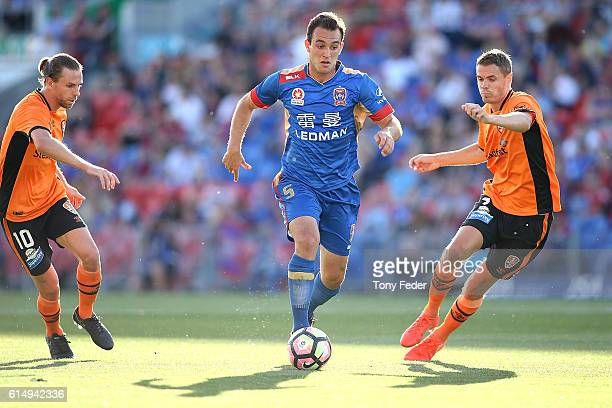 Benjamin Kantarovski of the Jets controls the ball from Brett Holman and Thomas Kristensen of the Roar during the round two ALeague match between the...