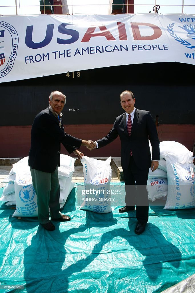 Benjamin Moeling (R), the charge d'affaires of the US embassy in Khartou, shakes hands with WFP Sudan chief Adnan Khan as a US aid shipment organised by the US Agency for International Development and the World Food Programme arrives at Port Sudan on the Red Sea coast, on May 5, 2016. Dockers began unloading tens of thousands of tonnes of food from a US aid ship destined for war-torn areas of Sudan, an AFP correspondent reported. The bulk carrier Liberty Grace docked in Port Sudan with a cargo of 47,500 tonnes of sorghum, a staple food in Sudan. SHAZLY