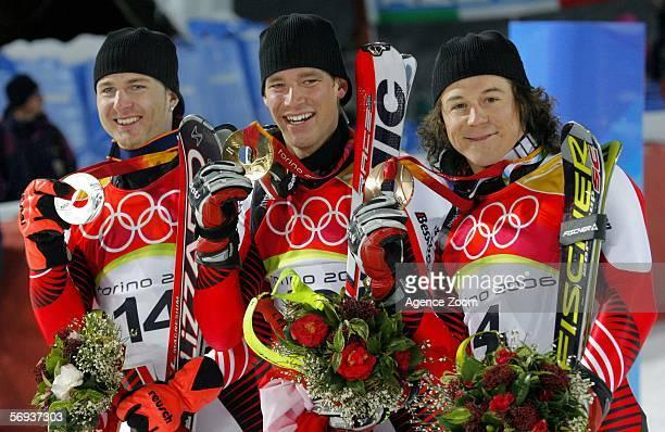Benjamin Raich of Austria celebrates the gold medal with bronze medallist Rainer Schoenfelder and silver medallist Reinfried Herbst in the Final of...