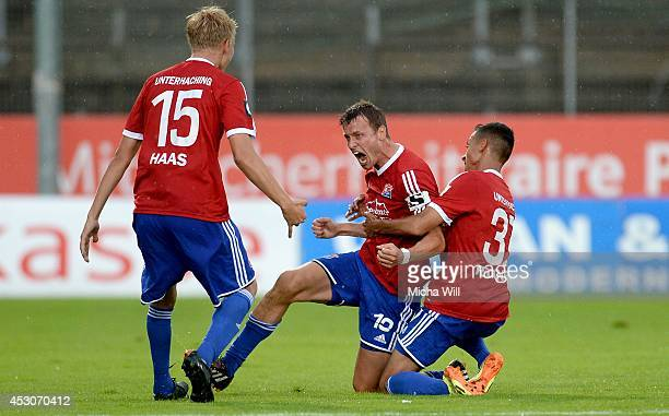 Benjamin Schwarz of Unterhaching celebrates with teammates after scoring his team's third goal during the Third League match between SpVgg...