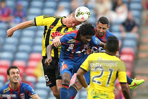 Benjamin Sigmund of the Phoenix heads the ball over Kew Jaliens of the Jets during the round 10 ALeague match between the Newcastle Jets and the...