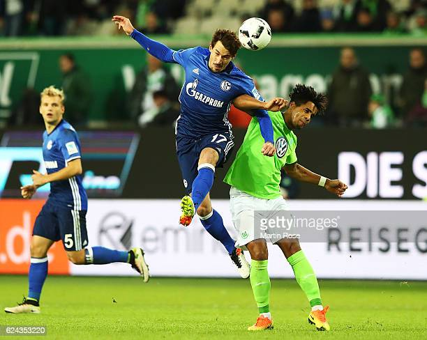 Benjamin Stambouli of Schalke 04 heads the ball over Daniel Didavi of VfL Wolfsburg during the Bundesliga match between VfL Wolfsburg and FC Schalke...