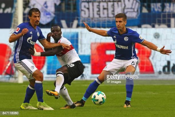 Benjamin Stambouli of Schalke and Chadrac Akolo Ababa of Stuttgart and Matija Nastasic of Schalke battle for the ball during the Bundesliga match...