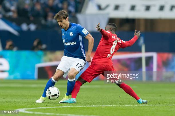 Benjamin Stambouli of Schalke and Naby Deco Keita of Leipzig battle for the ball during the Bundesliga match between FC Schalke 04 and RB Leipzig at...