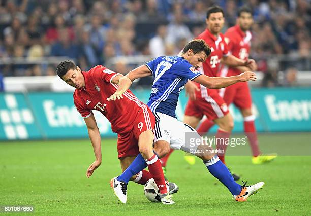 Benjamin Stambouli of Schalke and Robert Lewandowski of Bayern Muenchen in action during the Bundesliga match between FC Schalke 04 and Bayern...