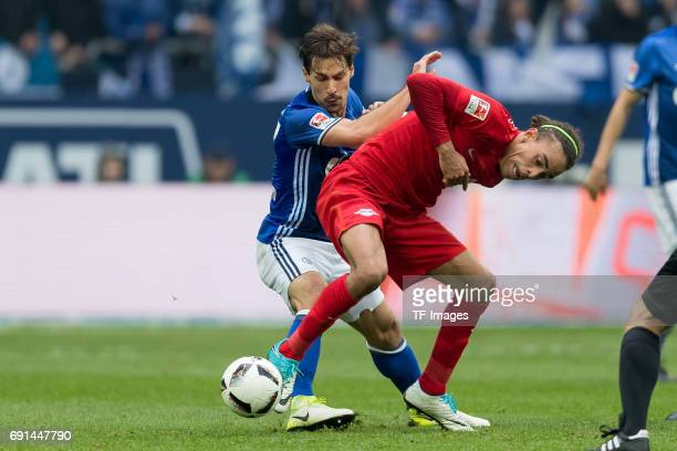 Benjamin Stambouli of Schalke and Yussuf Poulsen of Leipzig battle for the ball during the Bundesliga match between FC Schalke 04 and RB Leipzig at...