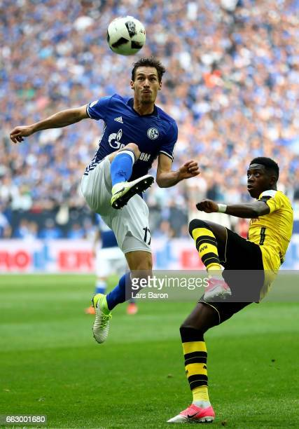 Benjamin Stambouli of Schalke challenges Ousmane Dembele of Dortmund during the Bundesliga match between FC Schalke 04 and Borussia Dortmund at...