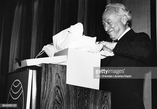 Benjamin Theodore Rome former President of George Hyman Construction Company standing and opening a gift box at a podium 1988