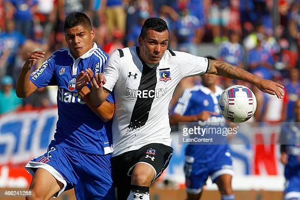 Benjam'in Vidal of Universidad de Chile struggles for the ball with Esteban Paredes of Colo Colo during a match between U de Chile and Colo Colo as...