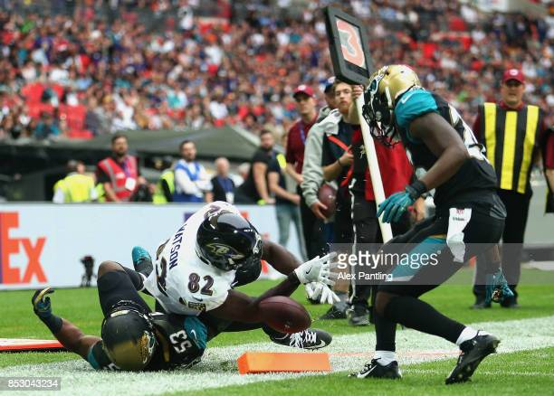 Benjamin Watson of the Baltimore Ravens breaks through Donald Payne of the Jacksonville Jaguars as he scores a touchdown during the NFL International...