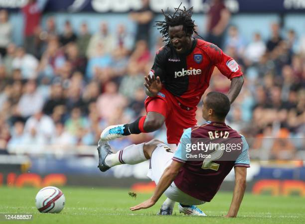 Benjani of Portsmouth is challenged by Winston Reid of West Ham United during the npower Championship match between West Ham United and Portsmouth at...