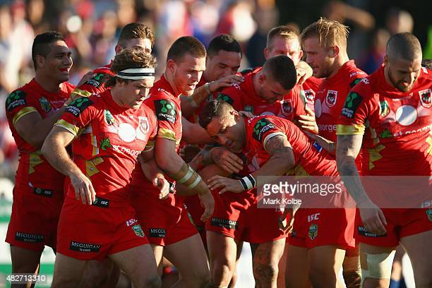 Benji Marshall of the Dragons celebrates with his team mates after scoring a try during the round 21 NRL match between the St George Illawarra...