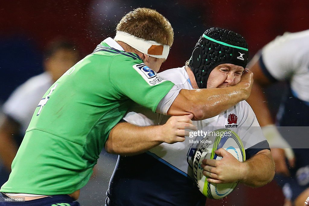 Benn Robinson of the Waratahs is tackled by Gareth Evans of the Highlanders during the Super Rugby trial match between the Waratahs and the Highlanders at Hunter Stadium on February 14, 2014 in Newcastle, Australia.