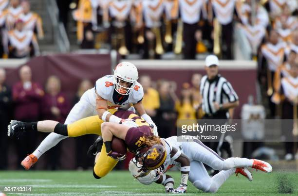 Bennett Williams and Stanley Green of the Illinois Fighting Illini tackles Ko Kieft of the Minnesota Golden Gophers during the second quarter of the...