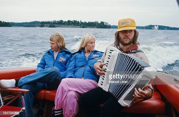 Benny Andersson playing the accordion in the back of a boat in the presence of Bjorn Ulvaeus and Agnetha Faltskog his wife