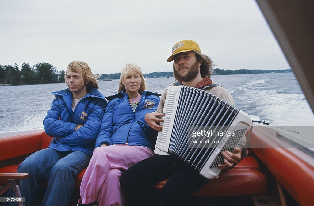 Benny Andersson playing the accordion in the back of a boat in the presence of Bjorn Ulvaeus and Agnetha Faltskog his wife.