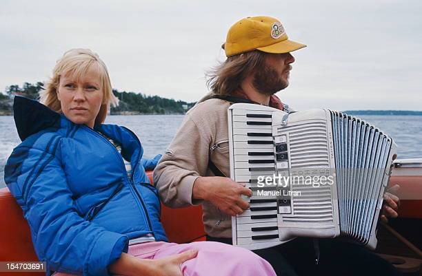 Benny Andersson playing the accordion in the back of a boat sitting for ratings Agnetha Faltskog