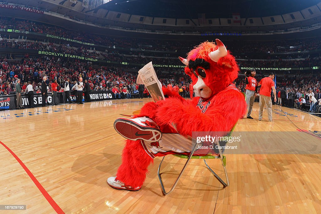 Benny the Bull sits backa and reads the paper before the game against the Brooklyn Nets in Game Three of the Eastern Conference Quarterfinals during the 2013 NBA Playoffs on April 25, 2013 at United Center in Chicago, Illinois.