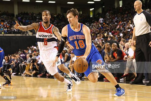 Beno Udrih of the New York Knicks drives against Eric Maynor of the Washington Wizards during the preseason game at the Baltimore Arena on October 17...