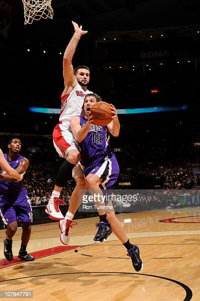 Beno Udrih of the Sacramento Kings drives against Linas Kleiza the Toronto Raptors during a game on January 9 2011 at the Air Canada Centre in...