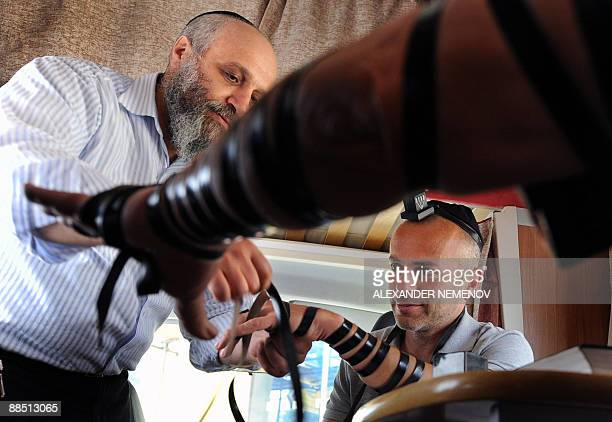 Benoit FINCKE Russian Rabbi Chaim Manklin places phylacteries on people's arms and heads inside his Mitzvah Bus in Moscow on June 16 2009 Two Rabbis...