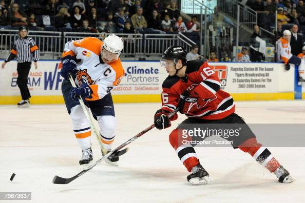 Benoit Mondou of the Lowell Devils and Mark Wotton of the Bridgepport Sound Tigers race for possession of the puck during the first period on...
