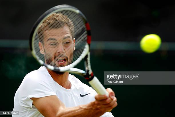Benoit Paire of France returns a shot during his Gentlemen's Singles third round match against Brian Baker the USA on day six of the Wimbledon Lawn...