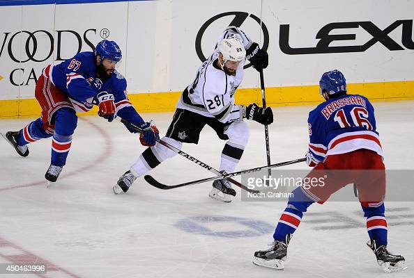 Benoit Pouliot and Derick Brassard of the New York Rangers tries to stop Jarret Stoll of the Los Angeles Kings in the third period of Game Four of...