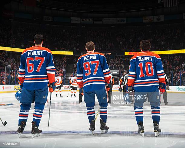 Benoit Pouliot Connor McDavid and Nail Yakupov of the Edmonton Oilers stand for the singing of the national anthem prior to a game against the...