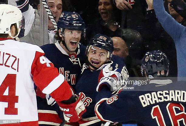 Benoit Pouliot Mats Zuccarello and Derick Brassard of the New York Rangers celebrate Zuccarello's game winning goal at 1402 of the third period...