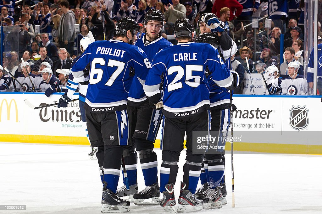 Benoit Pouliot #67, Matt Carle #25, Victor Hedman #77, Vincent Lecavalier #4 and Cory Conacher #89 of the Tampa Bay Lightning celebrate after Conacher scores the first goal of the first period of the Tampa Bay Lightning game against the Winnipeg Jets at the Tampa Bay Times Forum on February 1, 2013 in Tampa, Florida.
