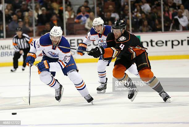 Benoit Pouliot of the Edmonton Oilers chases the puck against Cam Fowler of the Anaheim Ducks at Honda Center on April 1 2015 in Anaheim California