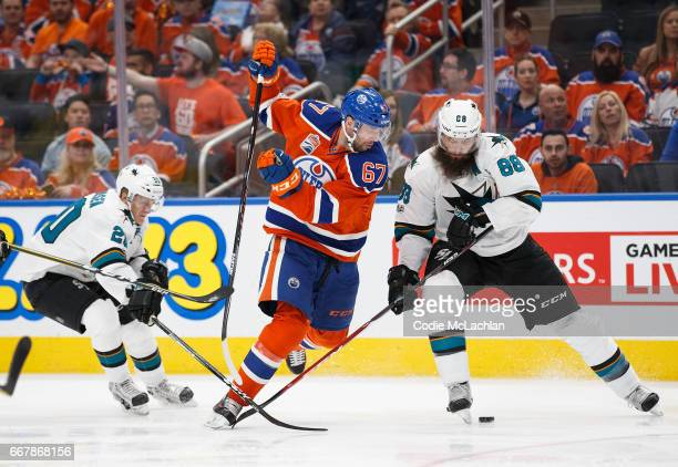 Benoit Pouliot of the Edmonton Oilers is tripped by Marcus Sorensen of the San Jose Sharks while battling Brent Burns in Game One of the Western...