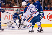 Benoit Pouliot of the Edmonton Oilers watches his shot go past goalie Ryan Miller of the Vancouver Canucks for a goal in NHL action on April 11 2015...