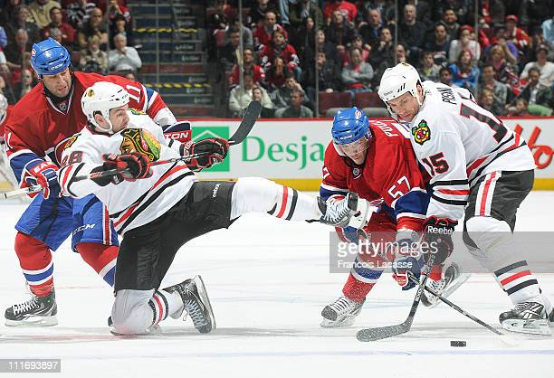 Benoit Pouliot of the Montreal Canadiens battles for the puck with Fernando Pisani of the Chicago Blackhawks during the NHL game on April 5 2011 at...