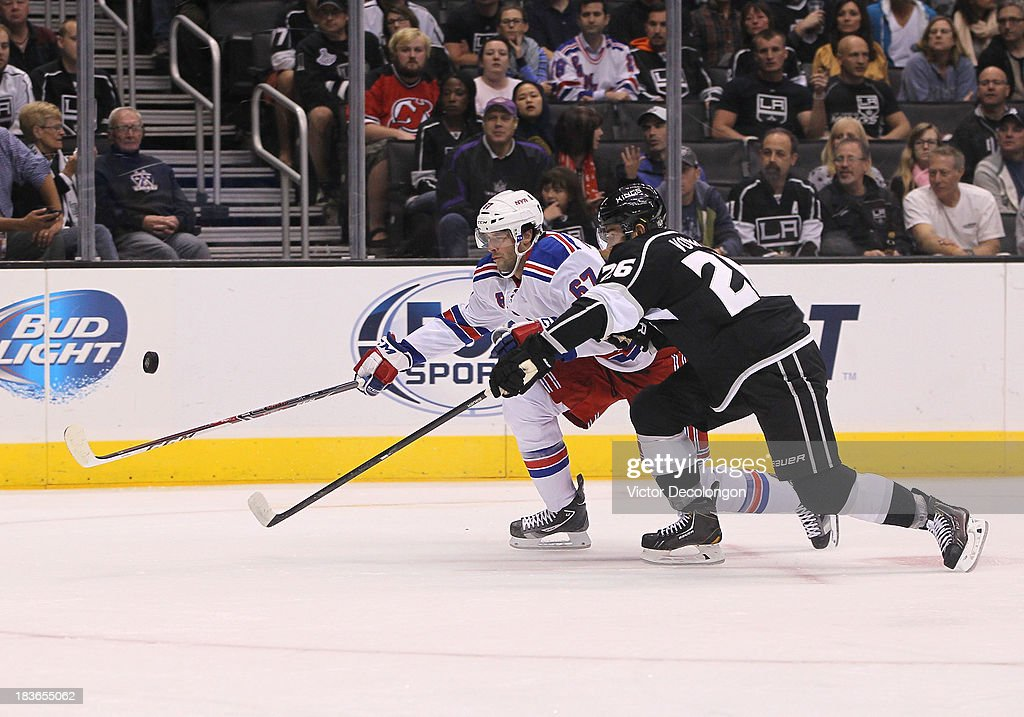 <a gi-track='captionPersonalityLinkClicked' href=/galleries/search?phrase=Benoit+Pouliot&family=editorial&specificpeople=879830 ng-click='$event.stopPropagation()'>Benoit Pouliot</a> #67 of the New York Rangers and <a gi-track='captionPersonalityLinkClicked' href=/galleries/search?phrase=Slava+Voynov&family=editorial&specificpeople=8315719 ng-click='$event.stopPropagation()'>Slava Voynov</a> #26 of the Los Angeles Kings skate vie for position to the puck during the NHL game at Staples Center on October 7, 2013 in Los Angeles, California. The Rangers defeated the Kings 3-1.