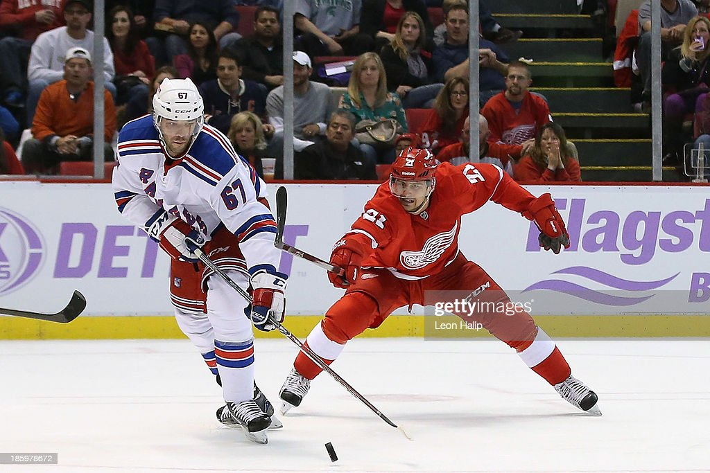 <a gi-track='captionPersonalityLinkClicked' href=/galleries/search?phrase=Benoit+Pouliot&family=editorial&specificpeople=879830 ng-click='$event.stopPropagation()'>Benoit Pouliot</a> #67 of the New York Rangers battles for puck control against <a gi-track='captionPersonalityLinkClicked' href=/galleries/search?phrase=Tomas+Tatar&family=editorial&specificpeople=5652303 ng-click='$event.stopPropagation()'>Tomas Tatar</a> #21 of the Detroit Red Wings during the third period of the game at Joe Louis Arena on October 26, 2013 in Detroit, Michigan. The Rangers defeated the Red Wings 3-2.