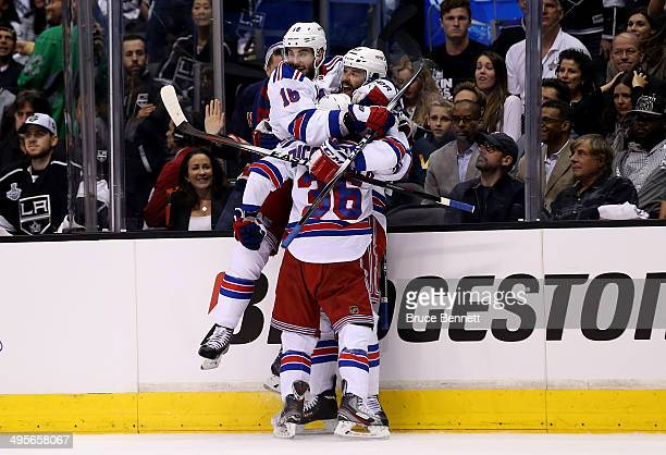 Benoit Pouliot of the New York Rangers celebrates with teammate Derick Brassard and Mats Zuccarello after Pouliot scores the first goal in the first...