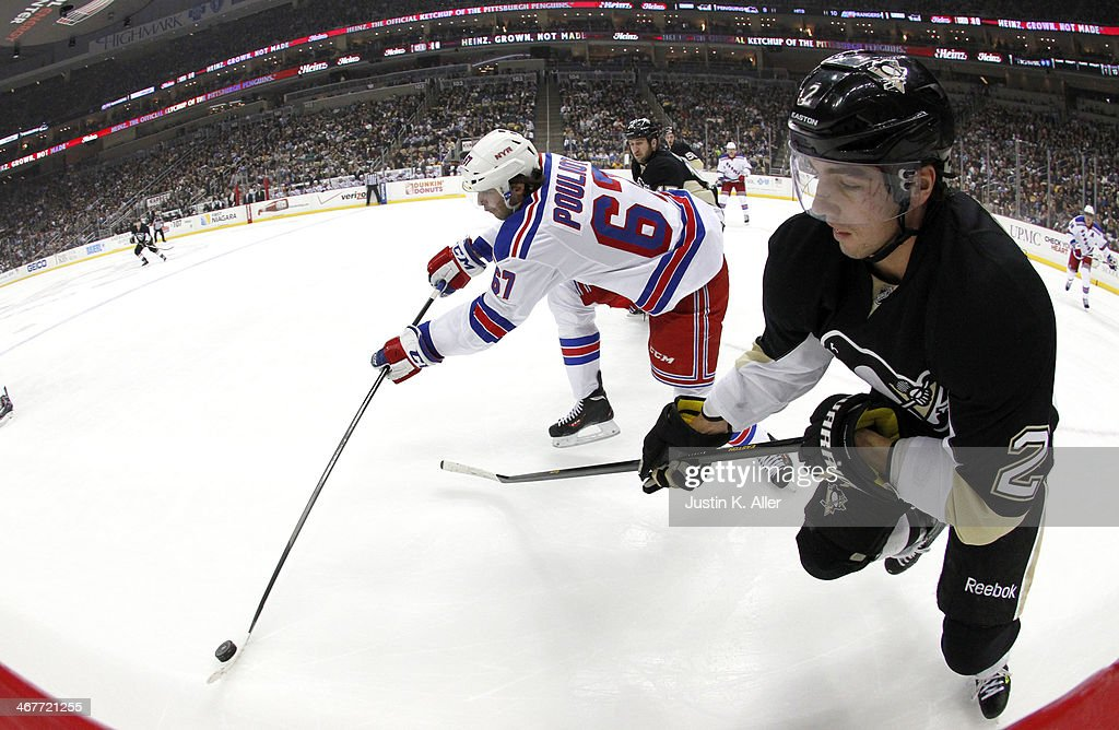 Benoit Pouliot #67 of the New York Rangers handles the puck in front of Matt Niskanen #2 of the Pittsburgh Penguins during the game at Consol Energy Center on February 7, 2014 in Pittsburgh, Pennsylvania.