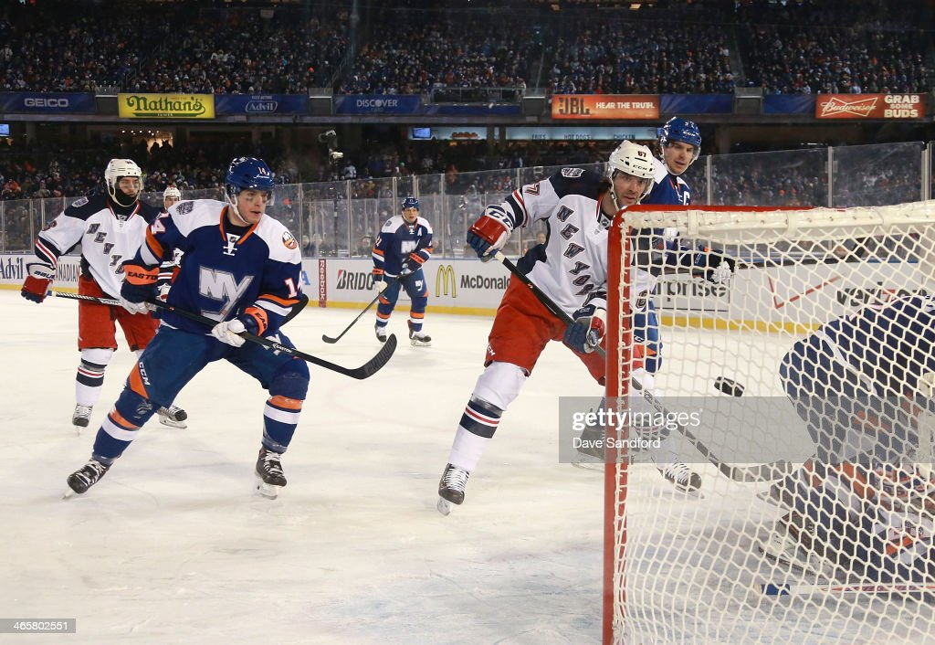 <a gi-track='captionPersonalityLinkClicked' href=/galleries/search?phrase=Benoit+Pouliot&family=editorial&specificpeople=879830 ng-click='$event.stopPropagation()'>Benoit Pouliot</a> #67 of the New York Rangers scores in the second period as Thomas Hickey #14 of the New York Islanders looks on during the 2014 Coors Light NHL Stadium Series at Yankee Stadium on January 29, 2014 in the Bronx borough of New York City.