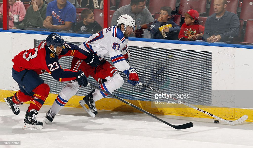 <a gi-track='captionPersonalityLinkClicked' href=/galleries/search?phrase=Benoit+Pouliot&family=editorial&specificpeople=879830 ng-click='$event.stopPropagation()'>Benoit Pouliot</a> #67 of the New York Rangers skates along the boards against <a gi-track='captionPersonalityLinkClicked' href=/galleries/search?phrase=Scott+Gomez&family=editorial&specificpeople=201782 ng-click='$event.stopPropagation()'>Scott Gomez</a> #23 of the Florida Panthers at the BB&T Center on November 27, 2013 in Sunrise, Florida.